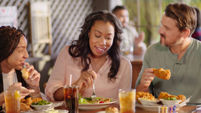 an interracial family eating fried chicken and southern food together in a restaurant