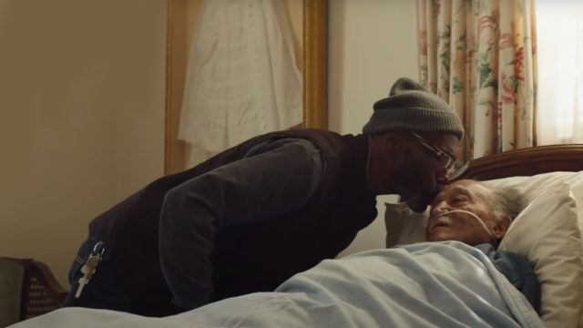 A man gently kisses an elderly man in a hospital bed on the forehead