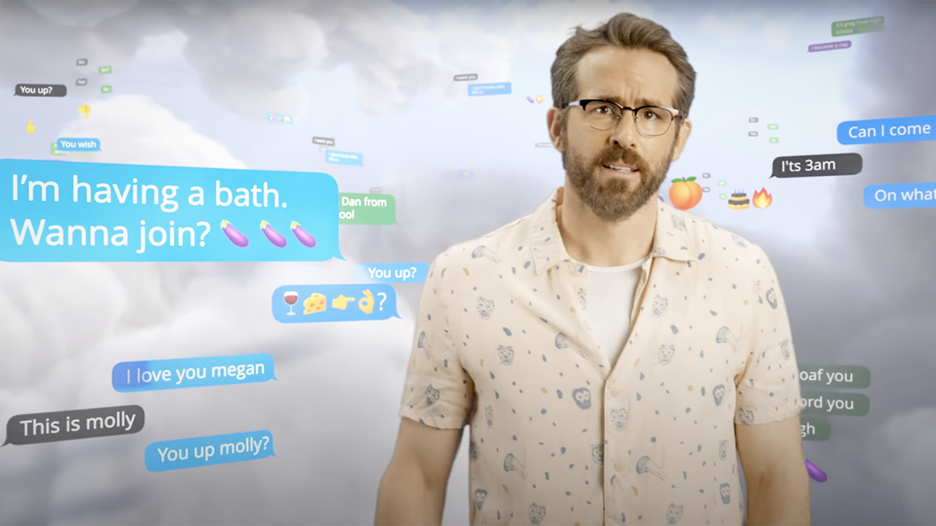 Ryan Reynolds talks to the camera while standing in front of a background of clouds and text messages such as I'm having a bath, want to join?