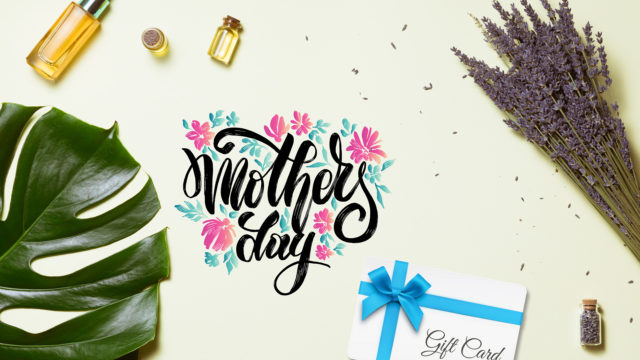 mother's day with essential oils and a gift card and plant leaves