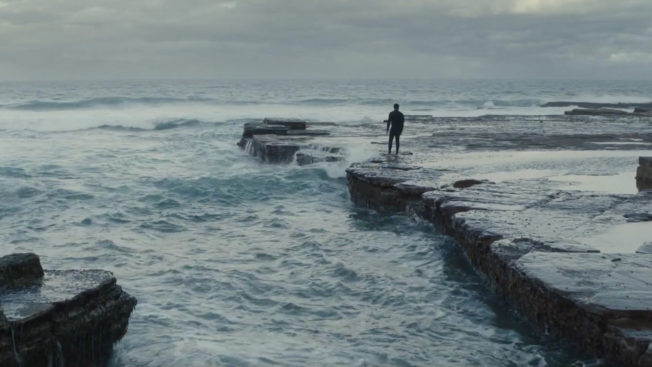 Man stands staring out to sea