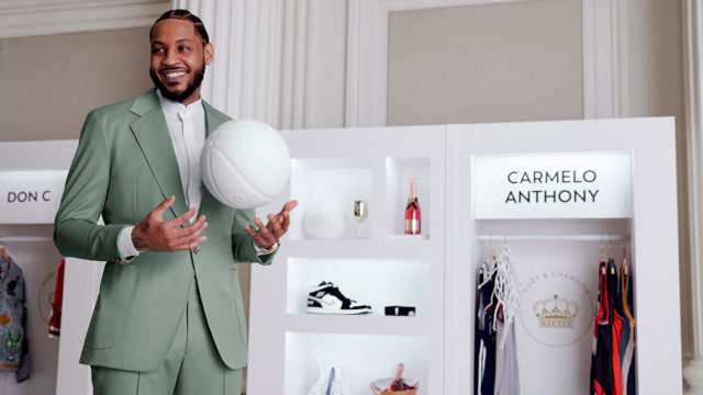 Suited Carmelo Anthony standing next to a display case