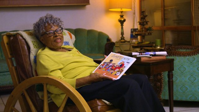 An elderly woman in a chair holding a book about Juneteenth