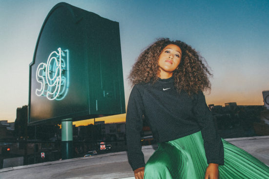 Naomi Osaka wears a green skirt in next to a Sweetgreen sign.