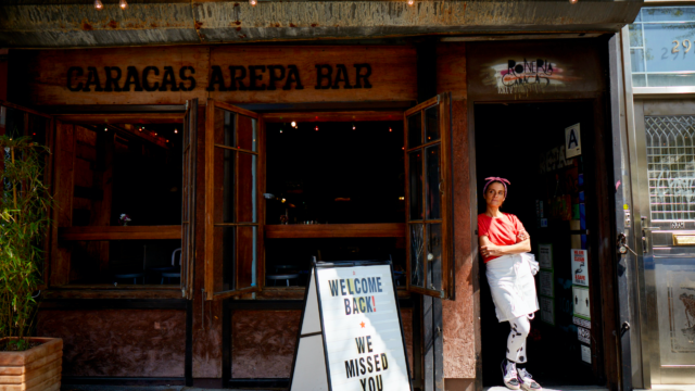 A woman standing in front of her restaurant