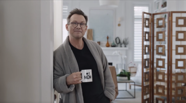 Christian Slater in a robe holding a mug that says