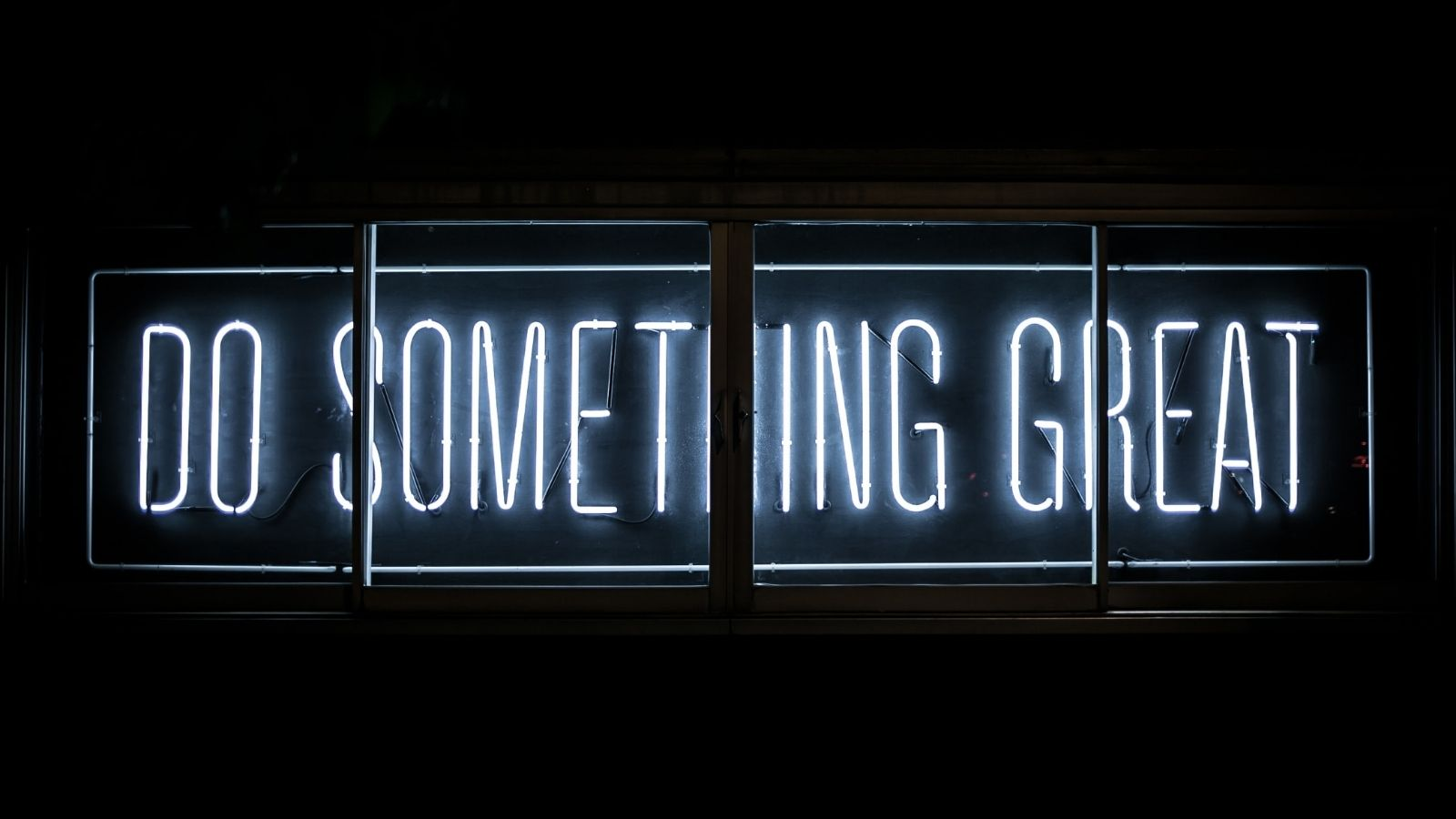 A neon sign reads 'Do Something Great'