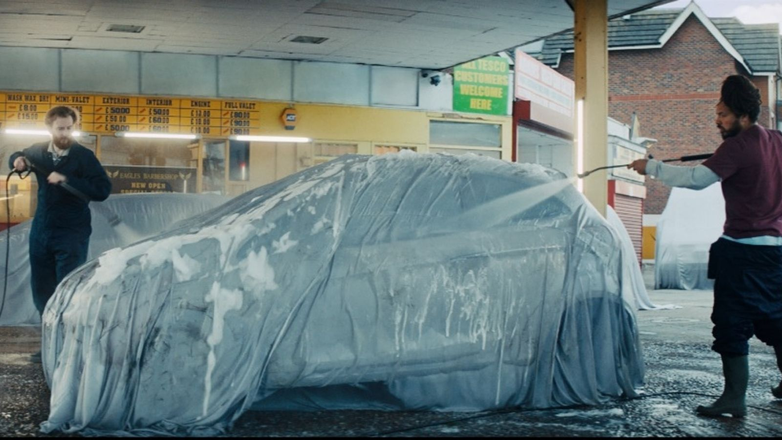 Men wash a car despite it being covered by a sheet