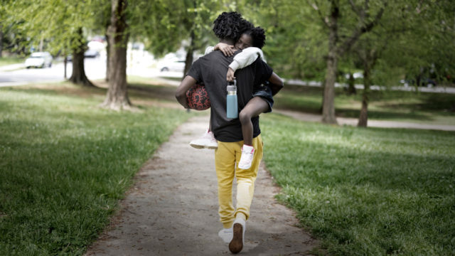 A father walking while carrying his daughter