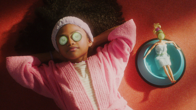 A child lounges with their Barbie doll