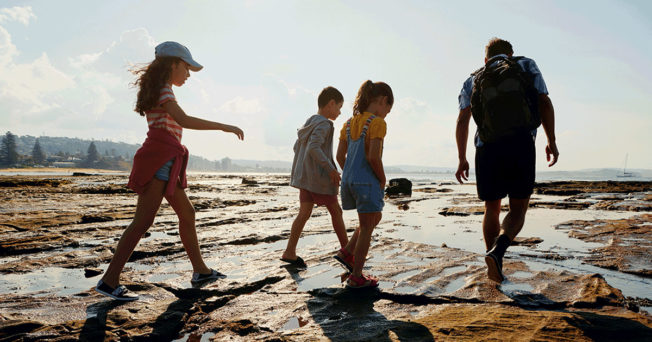 Father and three kids walking on a beach