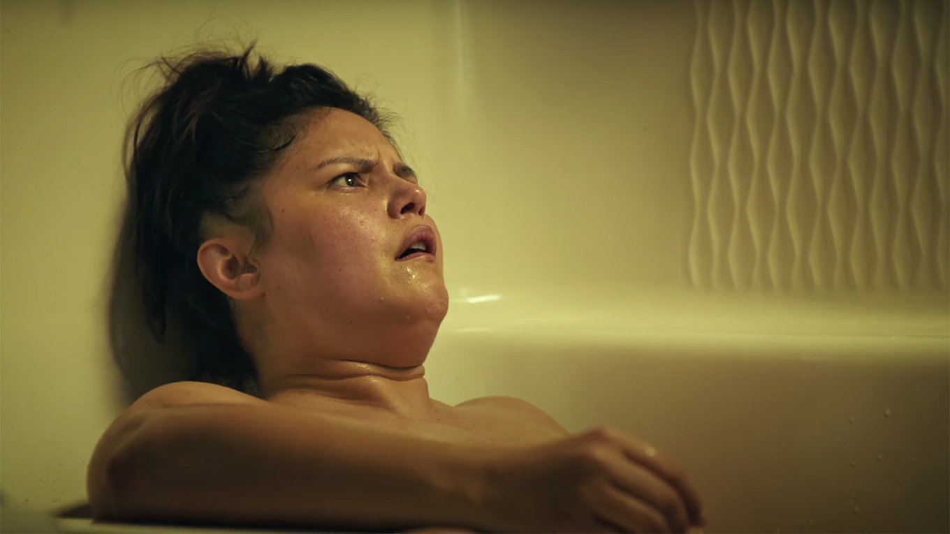 A woman in a sketchy hotel bath tub looks concerned