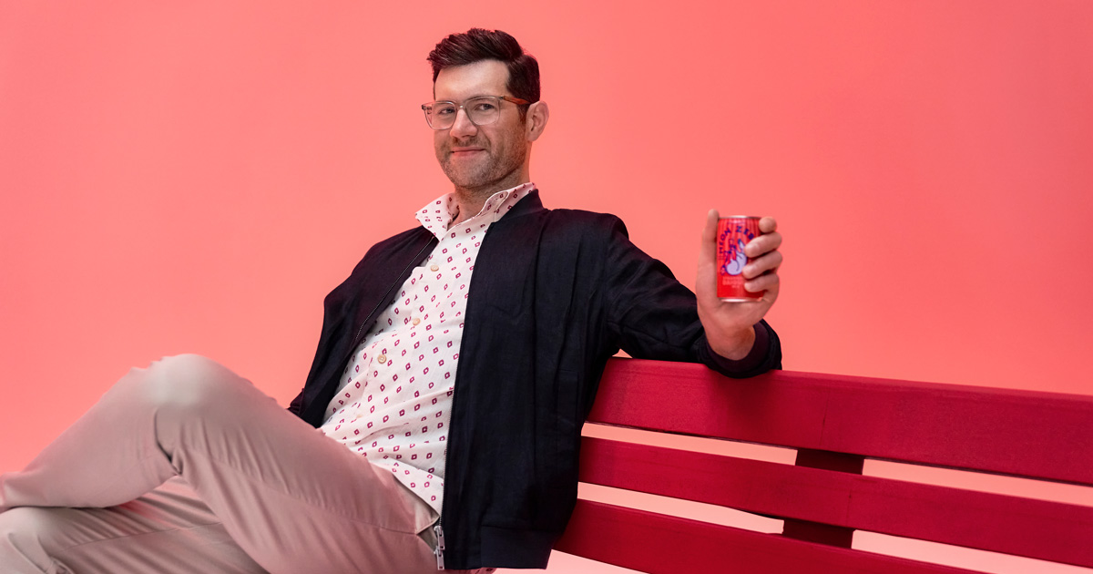 Billy Eichner sits on a bench holding a can of Neon Zebra