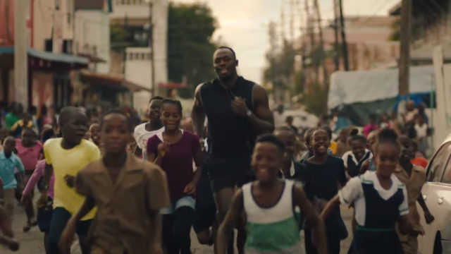 Usain Bolt runs with children as he prepares for the Olympic Games.