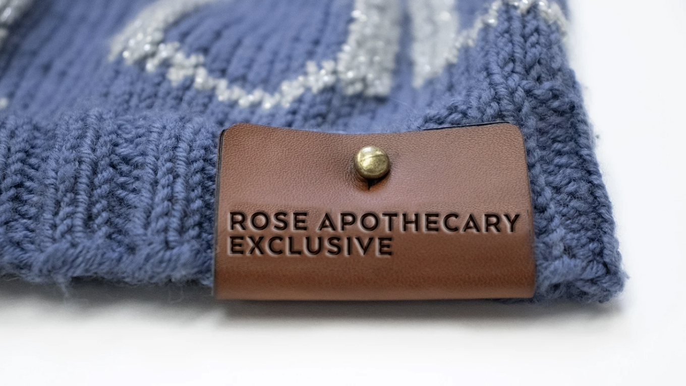A purple knitted garment is shown with the leather label saying Rose Apothecary Exclusive