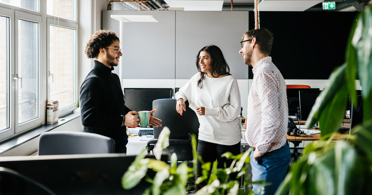 A small group of people chat in an office.