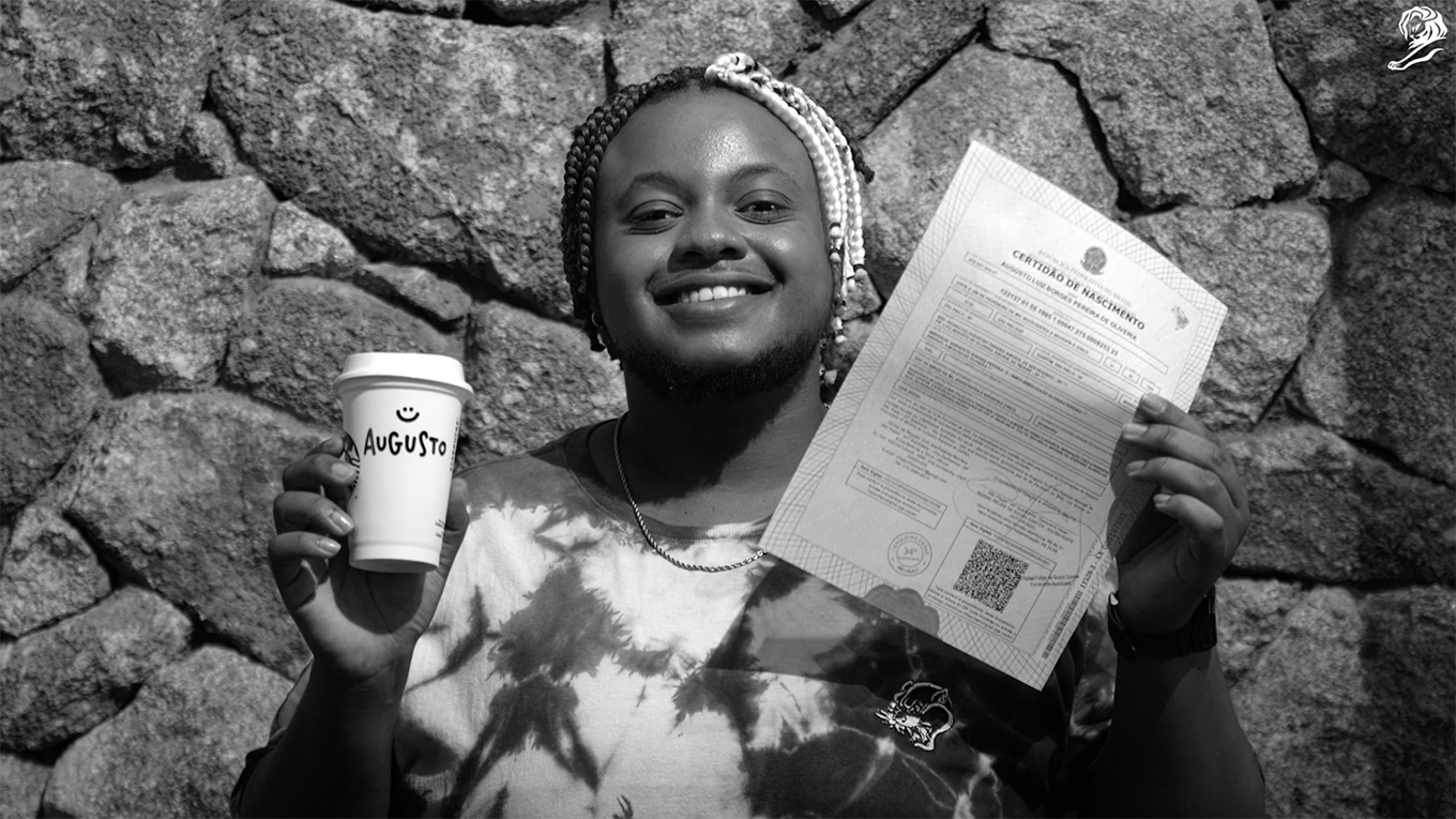 A trans person holding their Starbucks coffee and name-changing documents