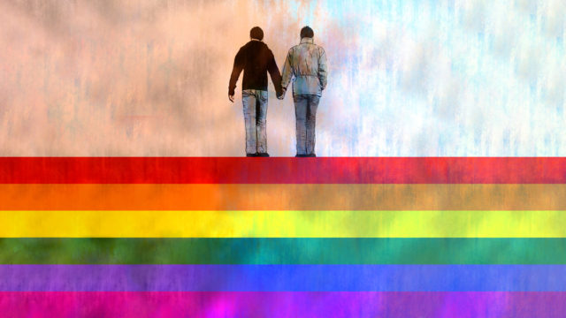 two people holding hands standing on a rainbow flag