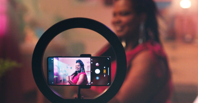 Smartphone within a circle light filming a woman