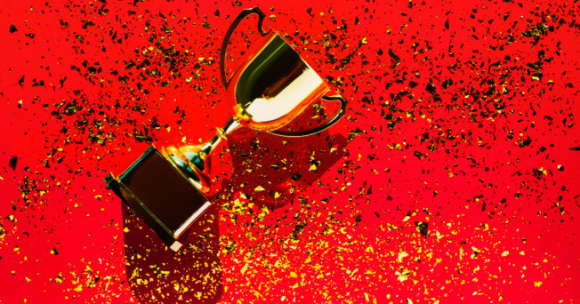 Top view of golden goblet on bright red background with sequin.