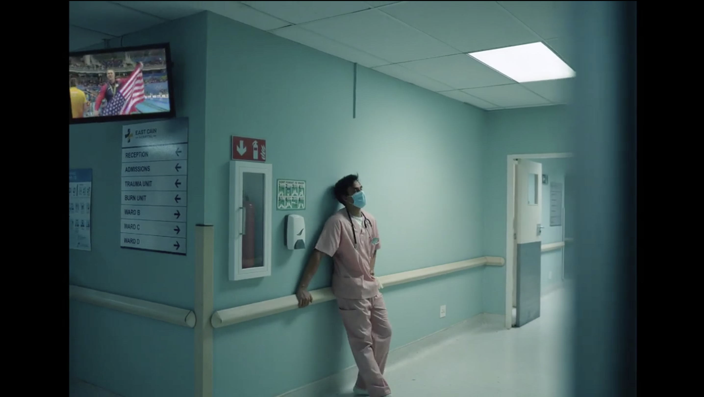 A doctor leans against a hospital wall as Olympics play in the background