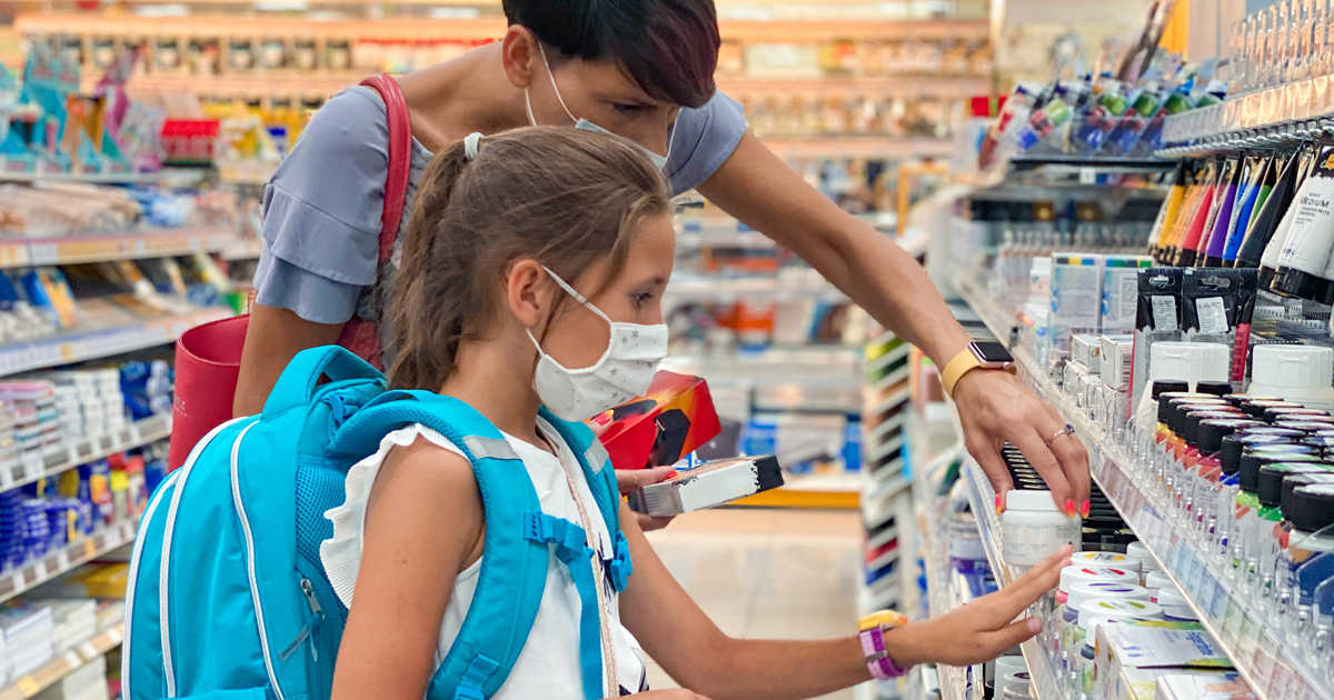 A parent and child pick out back-to-school supplies in a store