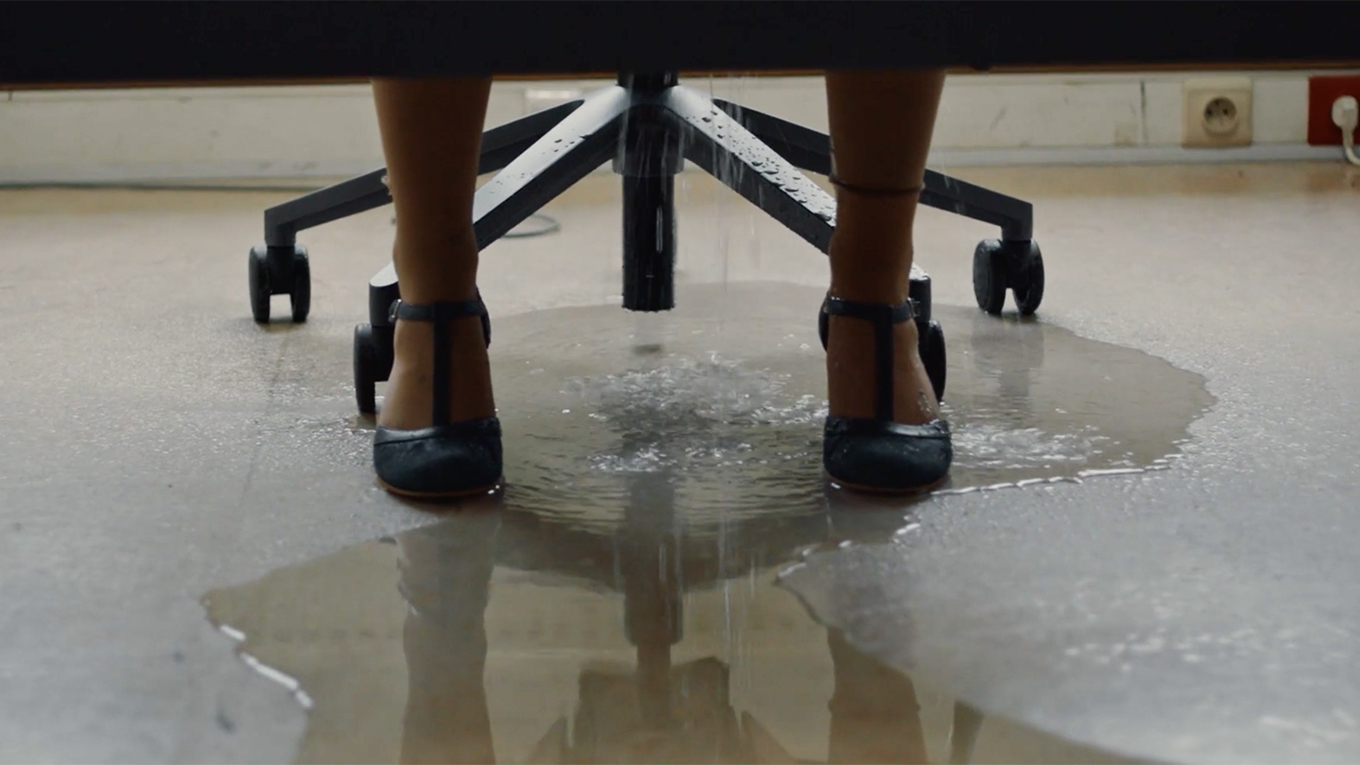 Water pools on the floor at a woman's fit as she sits at an office desk