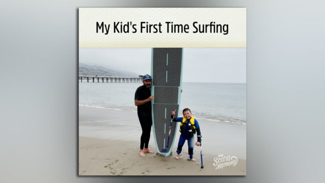 A man and a boy stand next to a surfboard