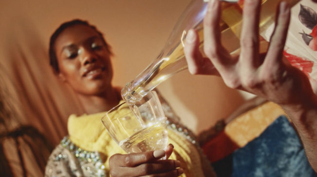 A person pours a glass of non-alcoholic wine