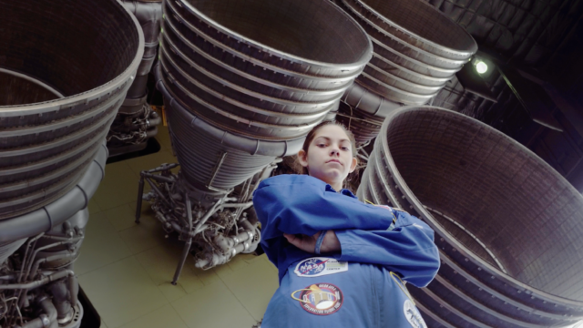 A young girl standing in front of rocket jets with her arms crossed