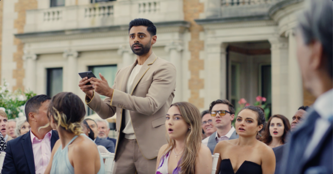 Hasan Minhaj standing in the middle of a seated crowd