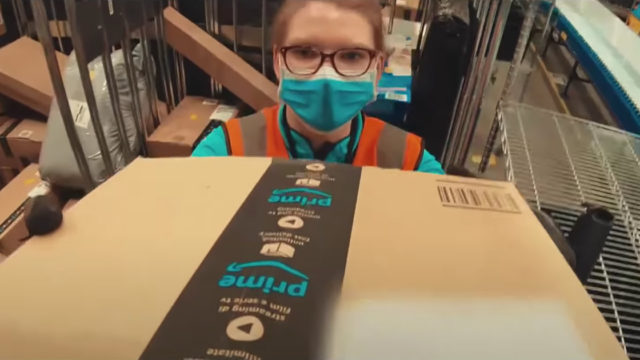 Image of Amazon worker with face mask handling packages.
