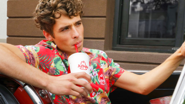 A man drinks from an Arby's cup while wearing the chain's summer Hawaiian shirt