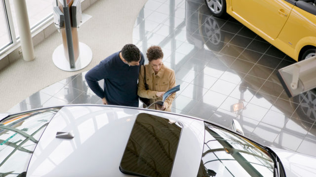 two people in a car dealership