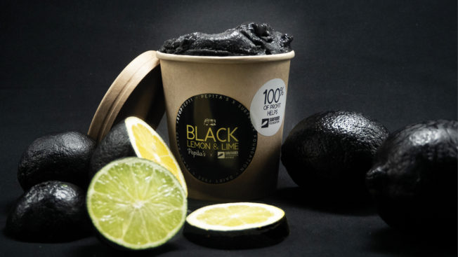 A pint of black ice cream sits next to lemons and limes whose rinds are painted black
