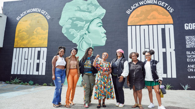 Women stand in front of a large mural that says 'Black Women Get Us Higher'
