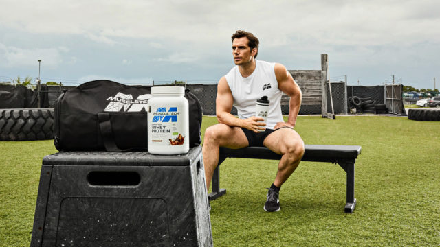 Henry Cavill on a bench behind MuscleTech products