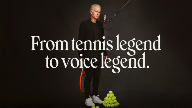 Tennis player John McEnroe stands in front of a microphone next to a pile of tennis balls