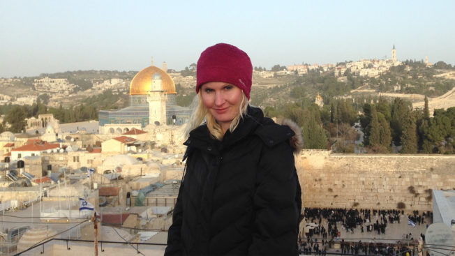 Larissa Faw is shown wearing a red hat and dark coat in Israel