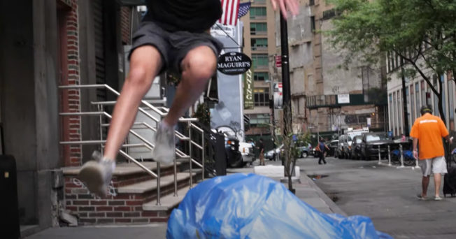 Man jumping over bags of trash