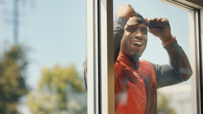 Football star Reggie Bush stands outside a Wendy's looking through the window