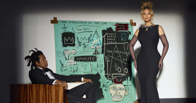 Photo of Beyonce and Jay-Z in black tie attire with Basquiat painting in the back in Tiffany's brand colors.