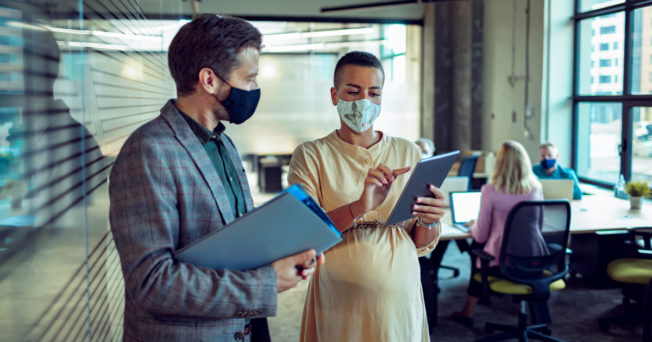 Two people in an office space wearing masks and talking