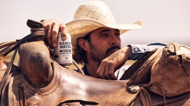 Actor and singer Ryan Bingham holds a can of Lone River Ranch Water while leaning against a horse saddle
