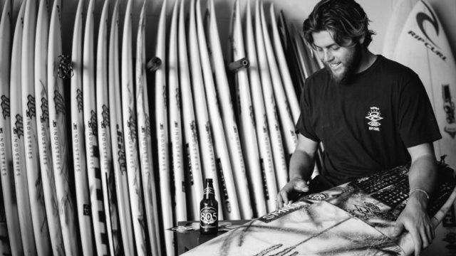 Conner Coffin waxing his surfboard