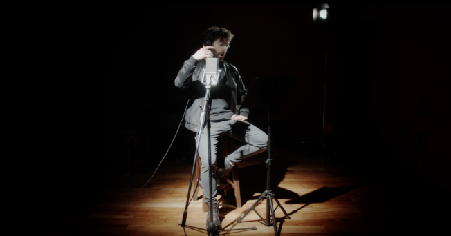 A man sits in a spotlight in front of a microphone