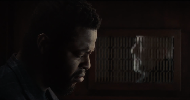 Winston Duke in a confessional booth