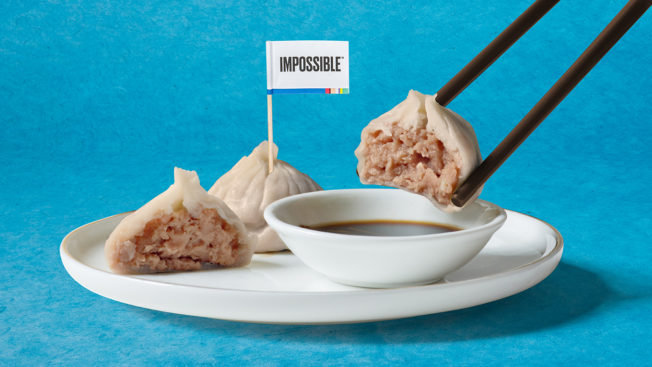 Asian dumplings made with Impossible plant-based pork are shown on a plate with chopsticks holding one dumpling