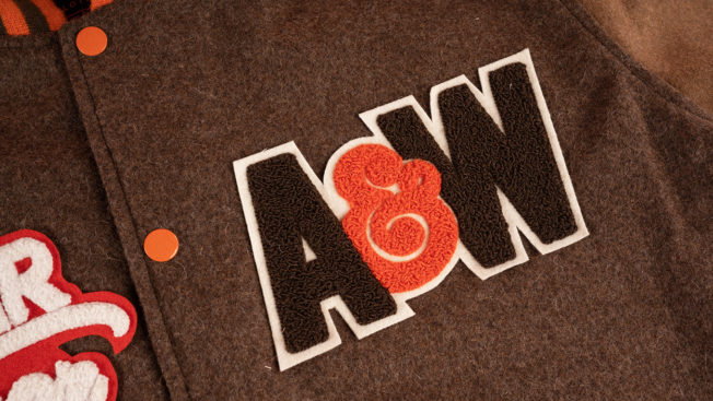 An A&W logo is shown stitched onto a brown varsity jacket
