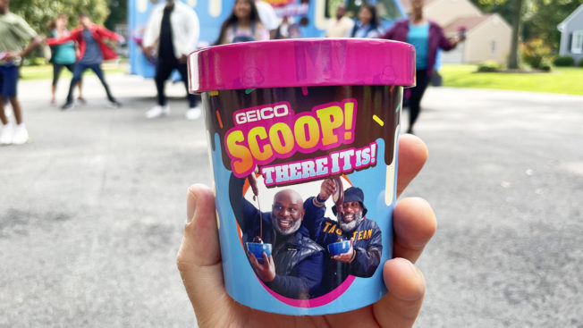 A hand holds a pint of Geico's Scoop, There It Is ice cream while people stand in the background